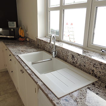 Bianco Antico granite with a ceramic inset sink, upstands and window sill - granitecraft shropshire