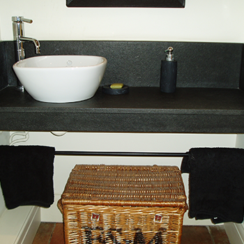 Riverwashed black granite, with upstand, an sit on sink for a cloak room - granitecraft shropshire