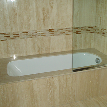 Botticino Classico for over the bath. Travertino marble tiles, walls and bath panel - granitecraft shropshire